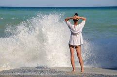 La jeune femme se tient sur la plage de mer et regarde Photos libres de droits