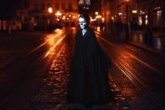 La jeune femme se tient sur la rue dans le costume noir avec le maquillage de Halloween Portrait de Fulbody Photo stock