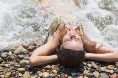 La jeune femme se trouve sur la plage Photographie stock