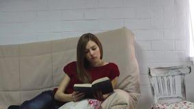 La jeune femme se trouve sur le sofa et le livre de lecture banque de vidéos