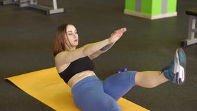 La jeune femme se trouve sur le tapis d'exercice faisant l'ABS en prenant ses mains et jambes dans le gymnase banque de vidéos
