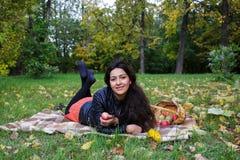 La jeune femme se trouve sur une couverture sur l'herbe en parc d'automne et sourit Photographie stock
