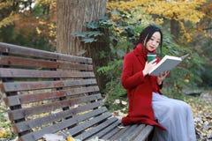 La jeune femme sensuelle asiatique lisant un livre reposent le banc dans le paysage romantique d'automne Portrait de fille assez  Images libres de droits