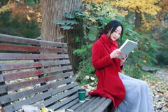 La jeune femme sensuelle asiatique lisant un livre reposent le banc dans le paysage romantique d'automne Portrait de fille assez  Photos libres de droits