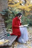 La jeune femme sensuelle asiatique lisant un livre reposent le banc dans le paysage romantique d'automne Portrait de fille assez  Photographie stock