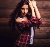 La jeune femme sensuelle et de beauté dans des vêtements sport posent sur le fond en bois grunge Photo stock