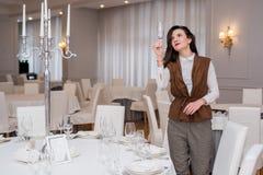 La jeune femme sert une table de fête dans un restaurant regardant par le verre photo libre de droits
