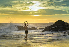 La jeune femme seule seul se tient sur la plage regardant vers la fin du vaste horizon Photos libres de droits