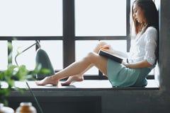 La jeune femme sexy dans la chemise et la jupe s'assied sur des WI de filon-couche de fenêtre photos libres de droits