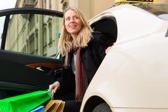 La jeune femme sort du taxi image stock