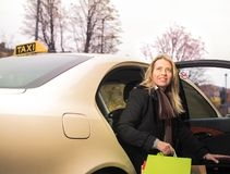 La jeune femme sort du taxi avec des paniers photos stock
