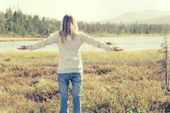 La jeune femme a soulevé des mains tenant le voyage extérieur seul de marche Photo libre de droits