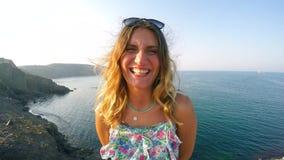 La jeune femme sourit - elle est aux collines et à côté de mer banque de vidéos