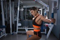 La jeune femme sportive établit sur l'appareillage de formation dans la classe de gymnase Concept de Halthy image stock