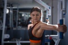 La jeune femme sportive établit sur l'appareillage de formation dans la classe de gymnase Concept de Halthy photo stock