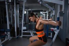 La jeune femme sportive établit sur l'appareillage de formation dans la classe de gymnase Concept de Halthy image libre de droits