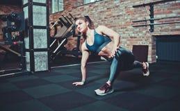 La jeune femme sportive avec le corps parfait dans les v?tements de sport fait des bouts droits pour des jambes dans le gymnase photos libres de droits