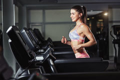 La jeune femme sportive courent sur la machine dans le gymnase Images stock