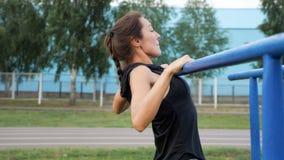 La jeune femme sportive dans les vêtements de sport a tiré sur la barre dehors photo libre de droits