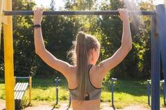 La jeune femme sportive de forme physique établissant au gymnase extérieur faisant la traction se lève au lever de soleil photos libres de droits