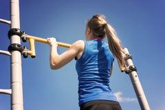 La jeune femme sportive de forme physique établissant au gymnase extérieur faisant la traction se lève au lever de soleil image stock