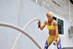 La jeune femme sportive faisant un certain crossfit s'exerce avec une corde o Photos stock