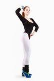 La jeune femme sportive rousse pose dans l'habillement noir et blanc de formation Image stock