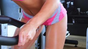 La jeune femme sportive s'est engagée sur un vélo stationnaire dans le gymnase banque de vidéos