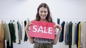La jeune femme stupéfaite montre le sac de vente à la caméra dans une salle d'habillement clips vidéos