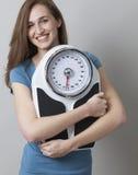 La jeune femme suivante un régime heureuse à son poids mesurent et silhouettent Images libres de droits