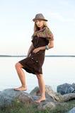 La jeune femme sur des pierres s'approchent de l'eau Photographie stock libre de droits