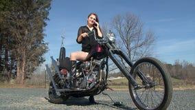 La jeune femme sur la moto parle au téléphone portable banque de vidéos