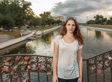 La jeune femme sur le pont avec amour ferme à clef sur la barrière Image stock