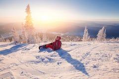 La jeune femme sur le surf des neiges repose la neige et attend l'instructeur pour patiner librement photo stock