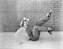 La jeune femme sur sembler au sol étonnée après avoir découvert que le patinage de rouleau est un sujet glissant (toutes les pers Image stock