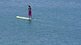 La jeune femme tiennent l'embarquement de palette dans le lac bleu clips vidéos