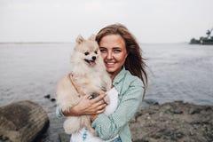 La jeune femme tient le chien dehors Images stock