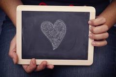 La jeune femme tient le tableau noir avec la forme de coeur là-dessus Photographie stock libre de droits