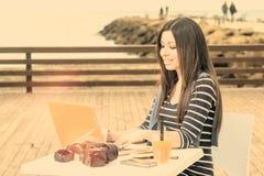 La jeune femme travaillant sur l'ordinateur portable à côté du filtre chaud de mer s'est appliquée photographie stock libre de droits