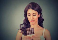 La jeune femme triste a fatigué des restrictions de régime implorant le chocolat de bonbons Image libre de droits