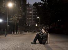 La jeune femme triste s'asseyant sur la rue a rectifié à seul désespéré de nuit photo stock