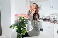La jeune femme a trouvé que le bouquet des roses sur la cuisine et le mari de appeler pour dire vous remercient Sourire enthousia photos stock
