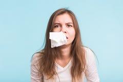 La jeune femme a un écoulement nasal sur le fond bleu Photographie stock