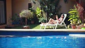 La jeune femme utilisant des lunettes de soleil utilisant le smartphone se trouvant sur le lit pliant par la piscine et le fils v banque de vidéos