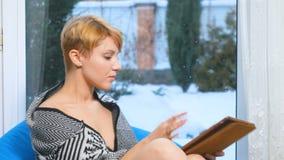 La jeune femme utilise le comprimé se reposant près de la fenêtre banque de vidéos
