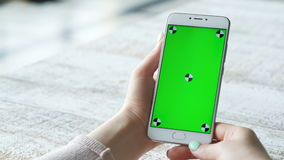 La jeune femme utilise le smartphone avec l'écran vert clips vidéos