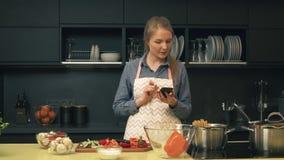 La jeune femme utilise le smartphone tout en faisant cuire banque de vidéos