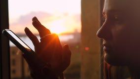 La jeune femme utilise le téléphone, se tenant à la fenêtre sur le fond d'un beau coucher du soleil avec la fusée du soleil Photographie stock libre de droits