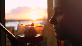 La jeune femme utilise le téléphone, se tenant au café de boissons de fenêtre sur le fond d'un beau coucher du soleil avec la fus Photo libre de droits