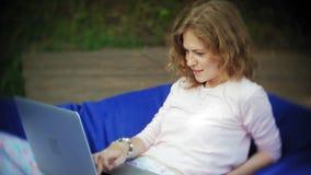 La jeune femme utilise un ordinateur portable, se trouvant dans un secteur de salon du parc sur les souffles mous banque de vidéos